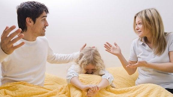 Kind sitzt zwischen streitenden Eltern auf einem Bett.