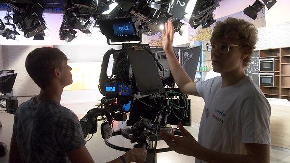 Ein angehender Mediengestalter erklärt einem Schüler die Bedienung einer Studio-Kamera.