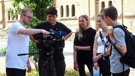 Schüler*innen lassen sich von einem Auszubildenden die Funktionsweise einer VJ-Kamera erklären.