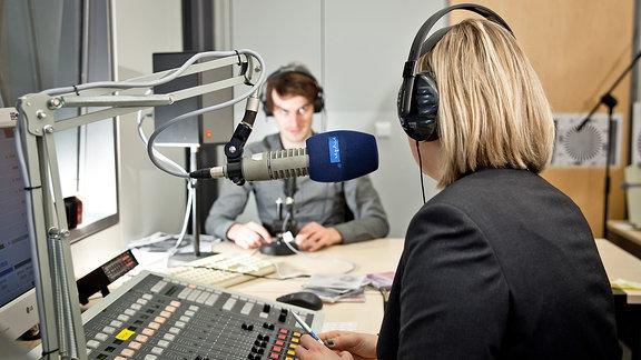 Ein Mann und eine Frau in einem Hörfunkstudio