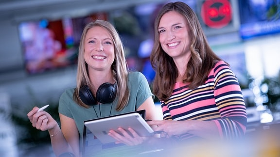 Zwei Frauen schauen von einem Clipboard auf und lachen.