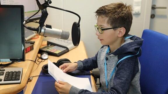 Ein Schüler sitzt vor einem Mikrofon.