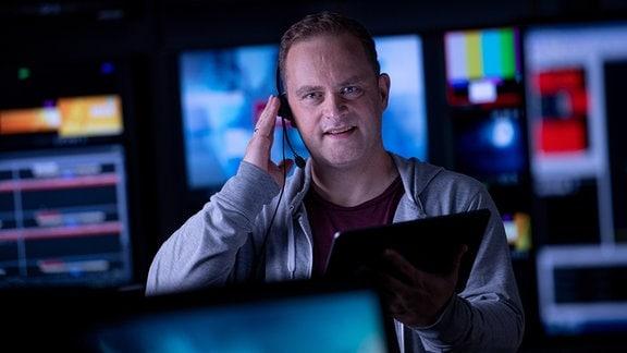 Ein Mann hat ein Headset auf. Im Hintergrund sind Bildschirme zu sehen.
