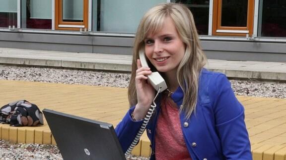 Mädchen sitzt mit Telefonhörer in der Hand und Laptop auf den Knien auf dem Fußboden.