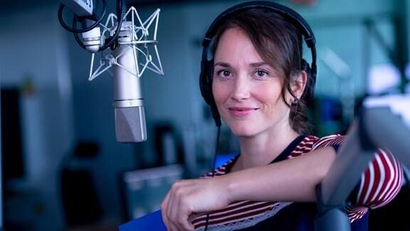 Eine Frau mit Kopfhörern steht vor einem Mikrofon.