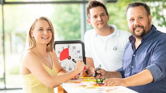 Drei Personen stehen an einem Tisch.