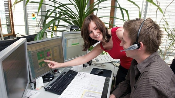 Eine junge Frau und ein junger Mann blicken auf einen Computerbildschirm.