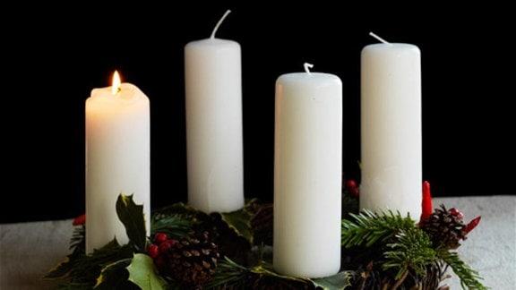 Ein Adventskranz mit einer brennenden Kerze.