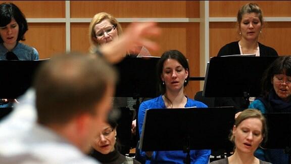 Mezzosopranistin Alexandra Schmid vor unscharfem Dirigenten Philipp Ahmann