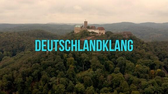 """Filmtitel """"Deutschlandklang"""" vor grünem Hügel mit Burg darauf"""