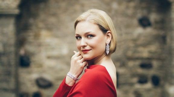 Sängerin Kai Rüütel in Abendgarderobe vor einem Gewölbebogen
