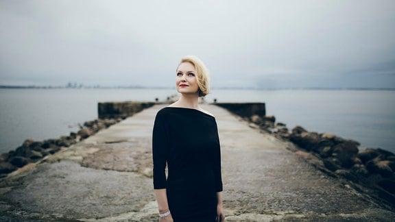 Sängerin Kai Rüütel schaut auf einer Mole in die Ferne