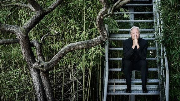 Dirigent Markus Stenz auf Treppe sitzend