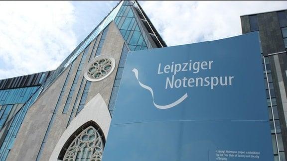 Eine Informationstafel der Leipziger Notenspur vor einem Universitätsgebäude am Augustusplatz in Leipzig.