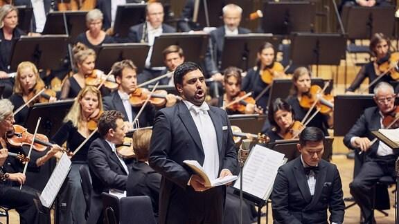 Bariton Milan Siljanov auf der Bühne vor MDR-Sinfonieorchester und MDR-Rundfunkchor beim Saisoneröffnungskonzert 2019/20 im Leipziger Gewandhaus