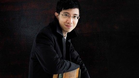 Dirigent Tung-Chieh Chuang auf einem Stuhl sitzend
