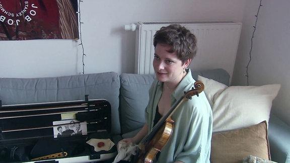 Eine Frau mit Geige sitzt auf ihrem Sofa.