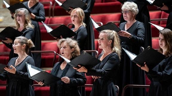 Die Damen des MDR-Rundfunkchors singen mit geöffneten Chormappen in den Händen.