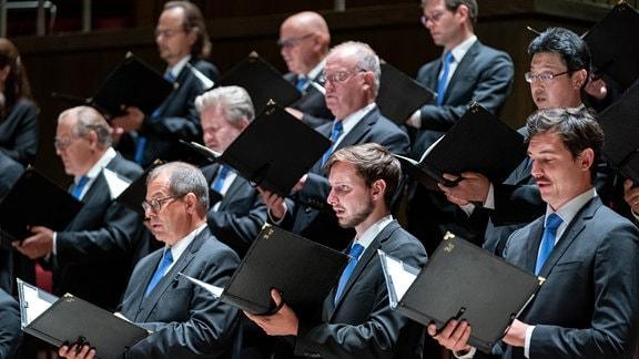 Die Herren des MDR-Rundfunkchors singen mit geöffneten Chormappen in den Händen.