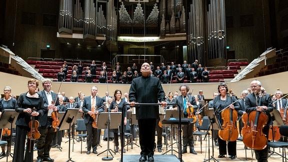 Das MDR-Sinfonieorchester und der MDR-Rundfunkchor mit Chefdirigent Dennis Russell Davies vorn mittig stehend beim Schlussapplaus im Gewandhaus.