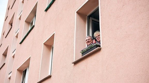 Lieder-Lieferdienst in Dessau: Konzert für die Eltern und Großeltern einer MDR-Hörerin vor ihrem Wohnhaus, Publikum blickt aus dem Fenster.