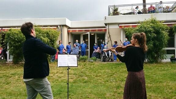 Annemarie Gäbler und Adam Markowski aus dem MDR-Sinfonieorchester bringen auf ihren Violinen ein Ständchen im Freien vor Menschen einer Pflegestation in einem Leipziger Krankenhaus.