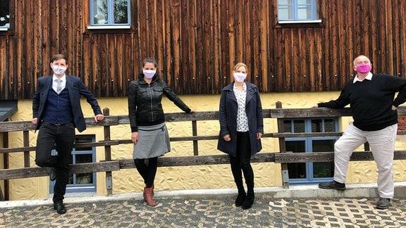 Vier Mitglieder des MDR-Rundfunkchors stehen vor einem Konzert des MDR Lieder-Lieferdiensts mit Mundschutzen an einem Geländer vor einem holzverkleideten Haus in Mittweida.