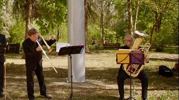Zwei Musiker stehen in der Natur und spielen