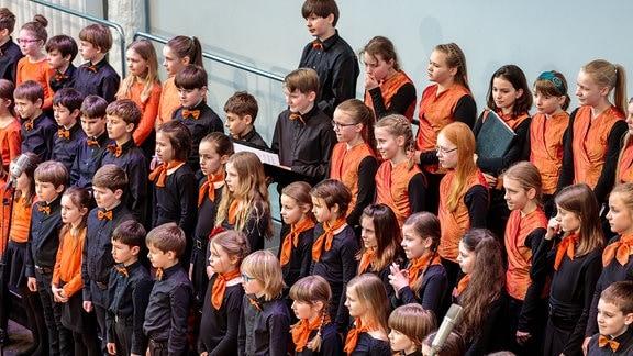 MDR-Kinderchor: Kinder verschiedener Altersstufen stehen in schwarz-roter Konzertkleidung auf der Bühne.