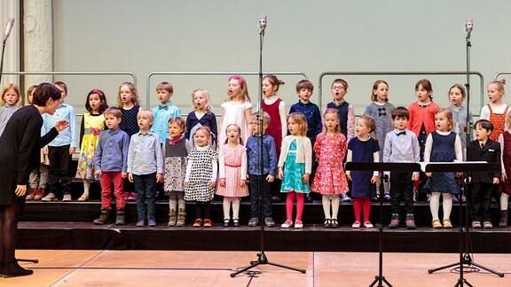 Kleine Kinder des MDR-Kinderchors im Vorschulalter stehen auf der Bühne, ihre Leiterin Meta Kuritz dirigiert.