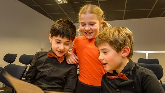 Drei Mitglieder des Nachwuchschor 1 des MDR-Kinderchors schauen gemeinsam in ein Notenheft.