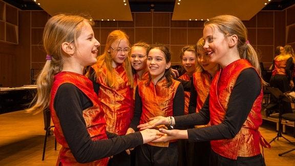 Mitglieder des Konzertchors des MDR-Kinderchors halten sich lachend an den Händen.