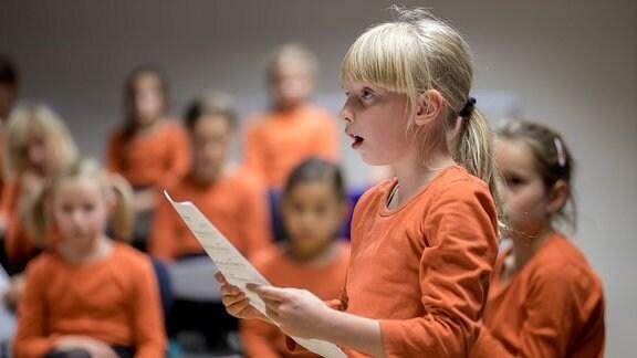 Ein Mädchen des MDR-Kinderchors singt allein, im Hintergrund der Chor.