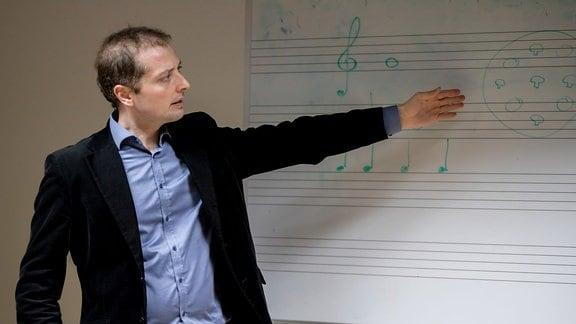 Ein Mann (Alexander Schmitt) steht an einer Tafel und zeigt auf Noten.