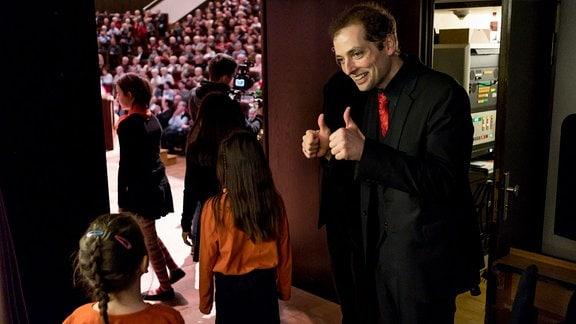Hinter den Kulissen laufen die Kinder des MDR-Kinderchors zur Bühne, an der Tür streckt ihr Dirigent Alexander Schmitt die Daumen nach oben.