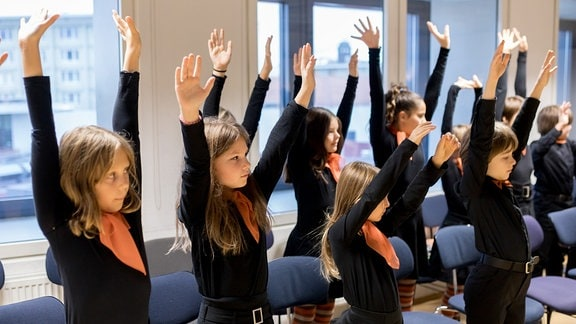 Die jungen Sängerinnen und Sänger des MDR-Kinderchors strecken beim Einsingen ihre Arme nach oben.