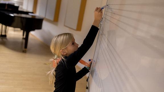 Ein Mädchen des Nachwuchschors 2 im MDR-Kinderchor schreibt etwas auf Notenlinien an eine Tafel.