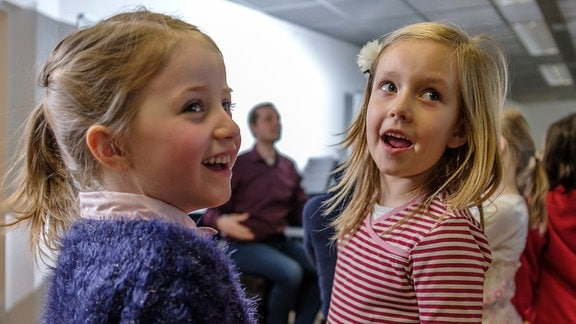 Zwei Mädchen des Vorchors im MDR-Kinderchor lachen.