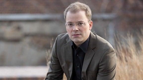 Philipp Ahmann, Künstlerischer Leiter des MDR-Rundfunkchors, sitzt auf einer Mauer