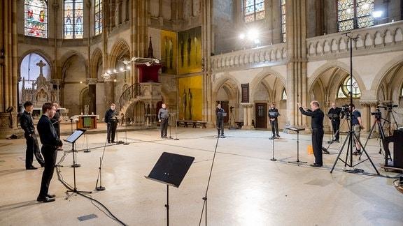 Mitglieder des MDR-Rundfunkchors stehen im großen Halbkreis in der Leipziger Peterskirche um Dirigent Philipp Ahmann und nehmen ein Werk von Michael Langemann auf.