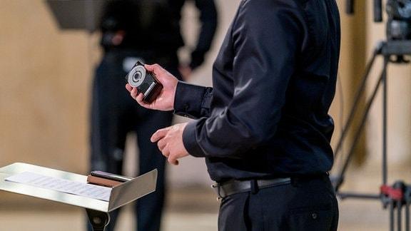 Ein Mann hält ein Metronom bei einer Produktion in der Leipziger Peterskirche.