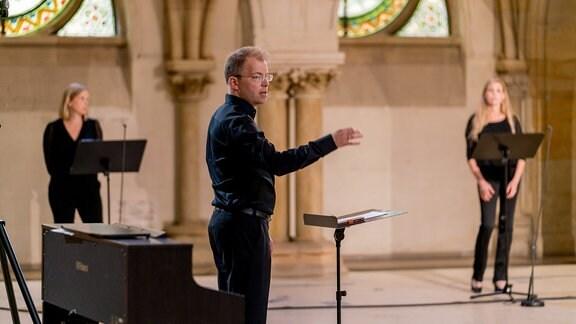 Philipp Ahmann dirigiert Mitglieder des MDR-Rundfunkchors bei einer Produktion in der Leipziger Peterskirche mit einem Werk von Michael Langemann.