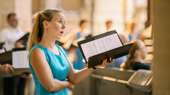 Altistin Karina Schoenbeck-Götz singend mit Chormappe in der Hand