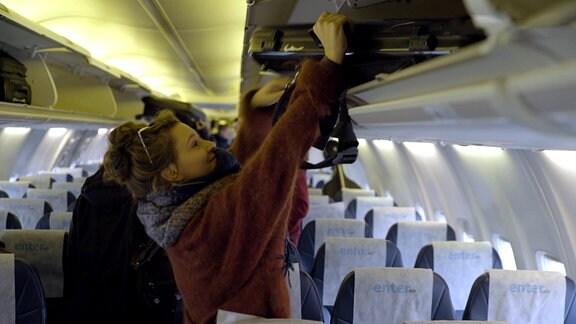 Eine Geigerin verstaut ihr Instrument im Gepäckfach in der Kabine eines Flugzeugs.