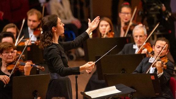 Oksana Lyniv dirigiert mit großer Geste beim Abschlusskonzert des MDR-Musiksommers in Suhl, im Hintergrund die Streicher des MDR-Sinfonieorchesters