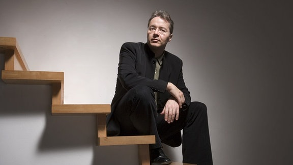 Stefan Asbury sitzt auf einer Treppe