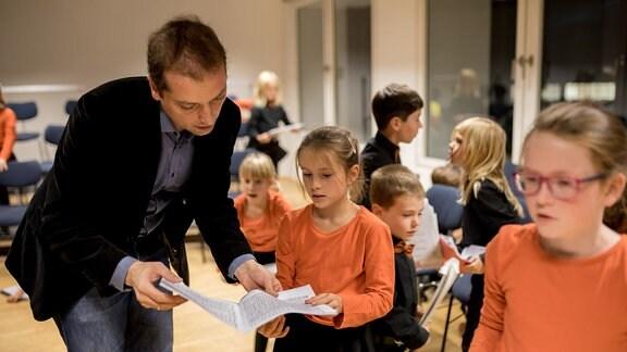 Dirigent Alexander Schmitt beugt sich mit Kindern des MDR-Kinderchors über Noten.