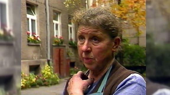 Eine Frau mit zugebundenen Haaren steht neben einem Wohnblock.