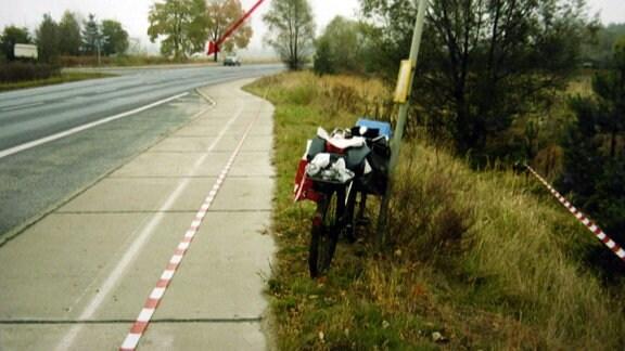 Ein Fahrrad steht angelehnt an einem Mast neben einer Straße.