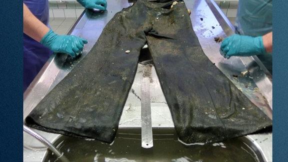 Eine nasse und verschmutzte Hose liegt ausgebreitet auf einem Obduktionstisch.